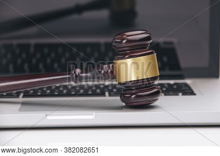 Closeup Of Laptop And Mallet On Table In Courtroom