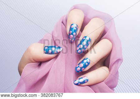 Female Hand With Pink Spotted Blue Nails Is Holding Pink Fabric On Striped Background, Manicure And