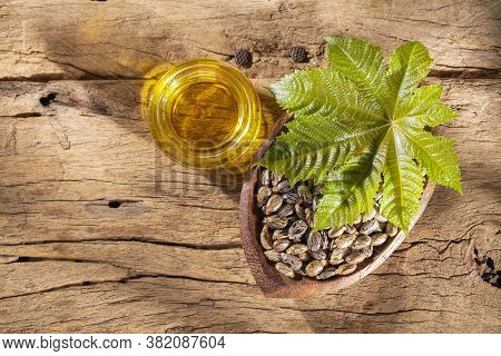 Castor Oil And Seeds, On Wooden Background