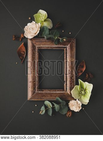 Autumnal-winter composition with vintage frame, dried leaves, bark of trees and berries on dark background.  Flat lay, copy space.