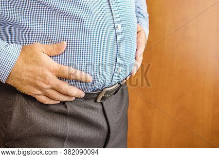 The Man Holds His Fat Big Belly With His Hands. Problem Of Obesity. The Concept Of Weight Loss. Heal