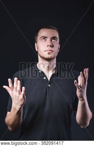 Portrait Of An Emotional Handsome Young Man, On A Black Background In The Studio, Who Is Gesturing.
