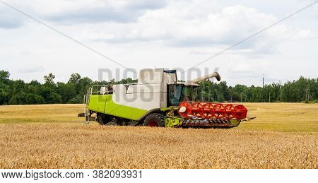 Modern Combine Harvester In Collection Of Wheat Grain, Prepare To Unload Seeds Into Truck. Harvestin