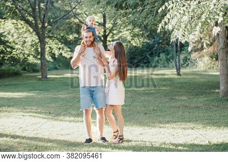 Happy Smiling Mother And Father With Baby Boy In Park Outdoor. Family Caucasian Mom And Dad With Son
