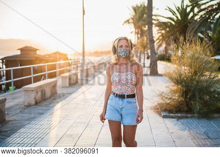 Attractive Blonde Woman With Headphones And Protective Mask Walking With Cheerful Attitude Along The