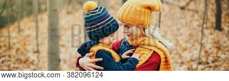 Caucasian Young Mother Hugging Talking To Cute Adorable Toddler Boy Son. Family In Autumn Fall Park