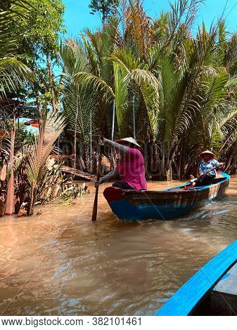 My Tho, Saigon, Vietnam: Tourist At Mekong River Delta Jungle Cruise With Unidentified Craftsman And