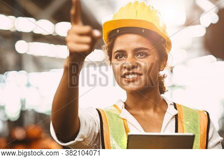 American Lady Worker In Factory Maintenance Engineer Happy Working Wearing Safety Uniform And Helmet