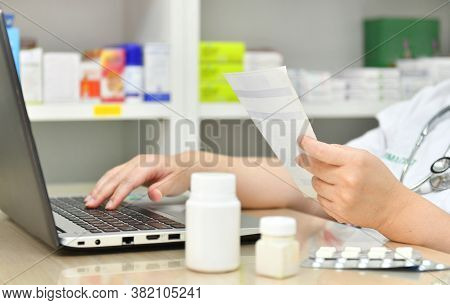 Pharmacist Using The Computer Laptop In Chemist Shop Or Pharmacy Drug Store. Hand Holding Medicine P