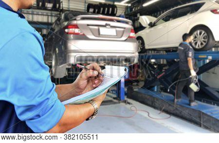 Mechanic Checks The Engine Repair List At The Garage
