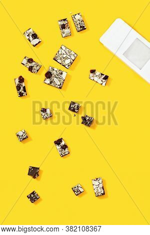 Bitten Chocolate Bar With Nuts And Dried Fruits Scattered Frome White Paper Packaging On Yellow Back