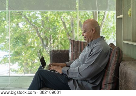Smiling Business Senior Old Elderly Black American Man, African Person Working From Home On Table Wi