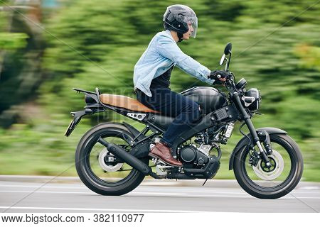 Serious Vietnamese Man Riding Fast On Motorcycle, Blurred Bushes In Background