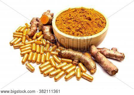 Raw Turmeric (curcuma Longa Linn) Herbal,curcuma Powder In Wooden Cup And Turmeric Capsules Isolated
