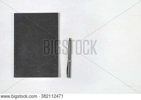 Top View Of Closed Black Cover Notebook With Shiny Pen On White Desk Background. Mock Up Copybook. M