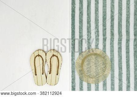 Concept Of Beach Holiday. Beach Flip-flops, Straw Hat. Beach Towel Striped Pattern. Summer Flat Lay.