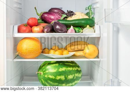Shelfs In The Refrigerator With Vegetables. Vegetables And Fruits In Refrigerator - Tomato, Eggplant