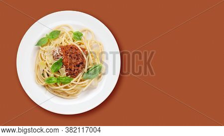 Spaghetti bolognese pasta with tomato and minced meat sauce, parmesan cheese and fresh basil. Top view flat lay with copy space