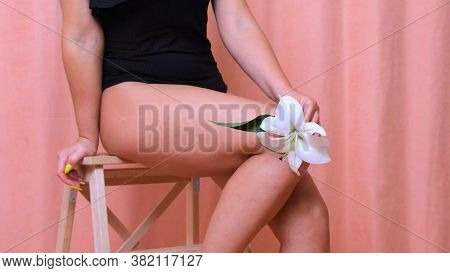 Close-up Of Beautiful Female Legs With Soft And Smooth Skin, Running A Flower With Her Hand On Her L
