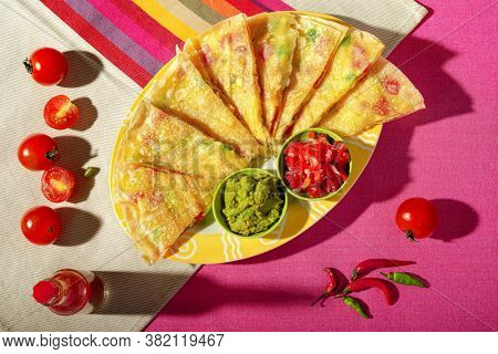 Mexican quesadilla with guacamole, tomatoes and chilli peppers on multi colored tablecloth.