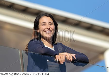 Happy Apartment Renter In A Balcony Looking At Camera A Sunny Day