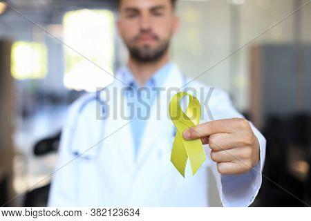 Doctor Hand With Yellow Gold Ribbon, Sarcoma Awareness, Childhood Cancer Awareness, World Suicide Pr