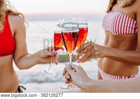Three Young Slender Women In Bikinis Are Chocking Glasses With Red Champagne On The Beach At Sunset.