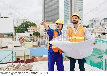 Builder Showing Finished Wall To Contractor With Building Blueprintin Hands