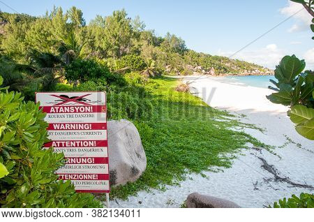 Warning Sign Post Of Strong Current At The Beach Of Petite Anse, La Digue Island, Seychelles