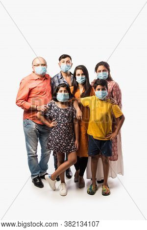 Indian Multigeneration Family Wearing Protective Medical Face Mask During Coronavirus And Flu Outbre