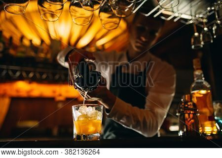 The Bartender Squeezes Citrus Juice Into A Cocktail.