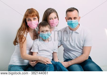 Young Family In Medical Masks During Home Quarantine.