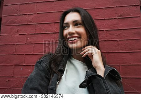 Image of beautiful cheerful happy young woman walking outdoors and looking away