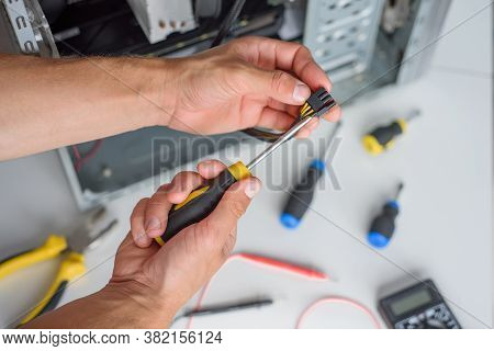 Male Hands Hold Pci-e Cord On The Computer Background