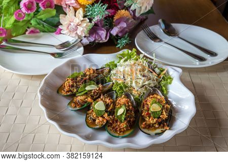 Mussels With Feta Cheese And Spicy Vegetables. Baked Mussels With Spicy Sauce. Garnished With Cherry