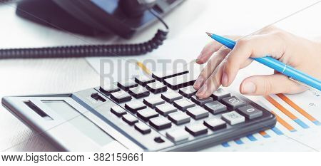Business And Communications. Calculator And Voip Phone In The Office, Close Up Of Hand. Finance Grap