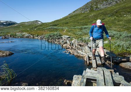 Hiking in Swedish Lapland. Man crossing river on small wooden broken bridge, Trekking alone in north Sweden. Arctic nature of Scandinavia in warm summer sunny day with blue sky