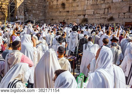 JERUSALEM, ISRAEL - SEPTEMBER 26, 2018:  Thousands of Jews, wrapped in tallits, pray at the Wailing Wall. Morning autumn Sukkot. The Jews hold four ritual plants.