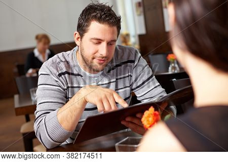 Man and woman choose menu from the menu in a restaurant