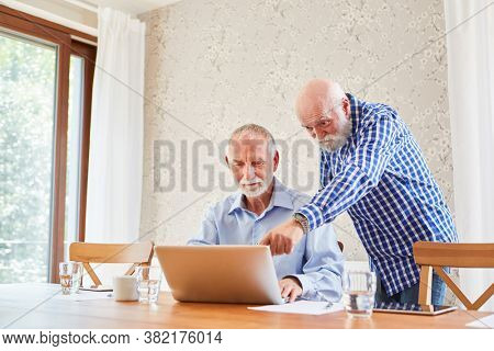 Two seniors in teamwork at laptop computer in a computer class