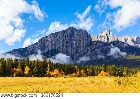 Bright autumn day in the Canadian Rockies. The Three Sisters Mountain is covered in lush white clouds. Canadian Banff National Park. The concept of active, ecological and photo tourism