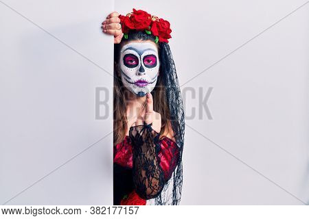 Young woman wearing day of the dead custome holding blank empty banner showing middle finger, impolite and rude fuck off expression