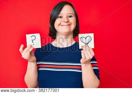 Brunette woman with down syndrome holding heart and question mark reminder smiling with a happy and cool smile on face. showing teeth.