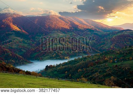 Foggy Morning In Autumn Mountains. Countryside Scenery In Fall Colors. Colorful Trees On The Hillsid