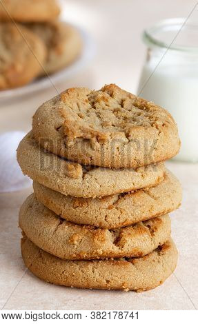 Peanut Butter Cookies In A Stack With Glass Of Milk And Plate In Background On A Table