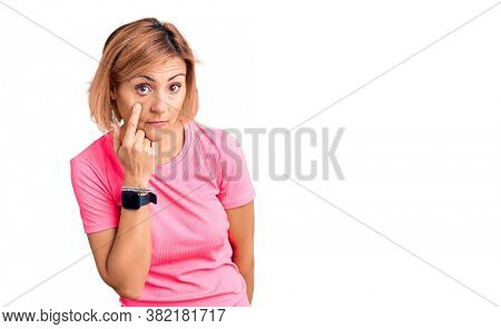 Young blonde woman wearing sportswear pointing to the eye watching you gesture, suspicious expression