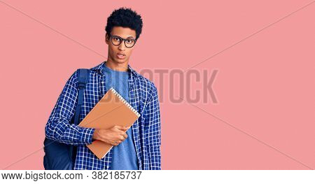 Young african american man wearing student backpack holding book in shock face, looking skeptical and sarcastic, surprised with open mouth