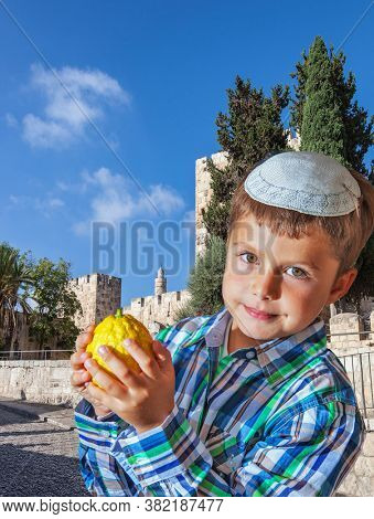 Jerusalem, Israel. Autumn Jewish holiday Sukkot. Beautiful Jewish boy with green eyes, in a white skullcap, with citrus in his hand