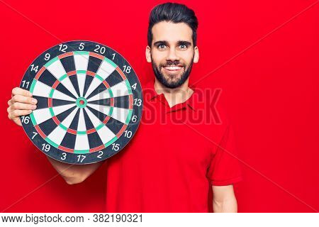 Young handsome man with beard holding dartboard looking positive and happy standing and smiling with a confident smile showing teeth