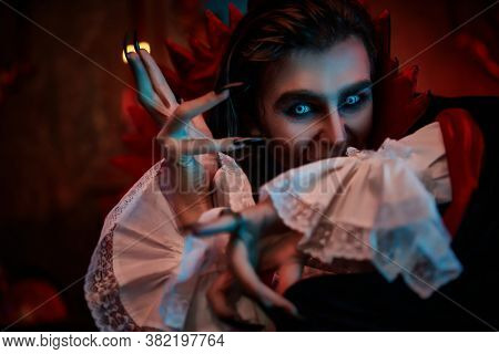Portrait of an insidious vampire sneaking through the night in an old castle. Traditional vampire man. Halloween.
